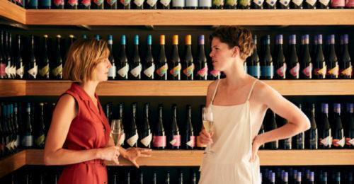 two women speaking with wine bottles