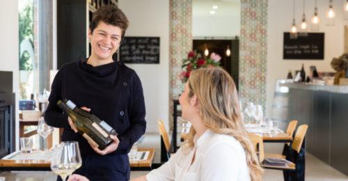 waitress presenting bottle to customer